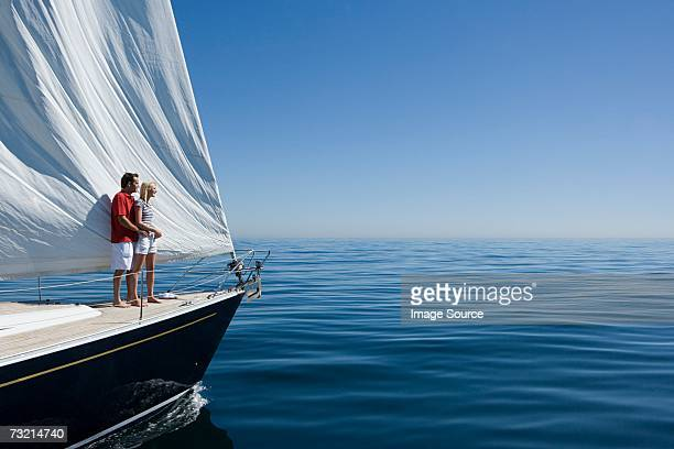 couple standing on a ships bow - yacht stock pictures, royalty-free photos & images