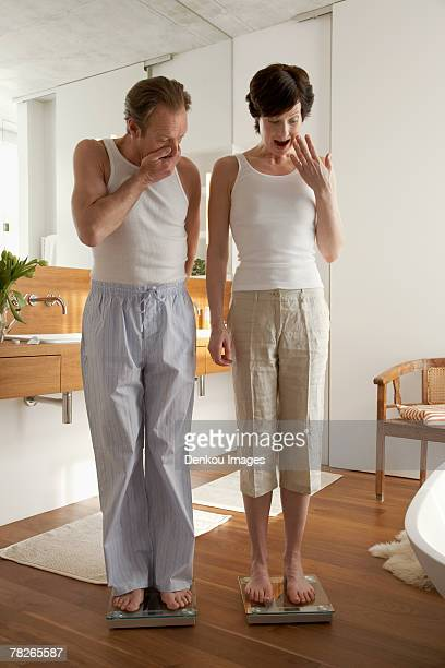 Couple standing on a weighing scale