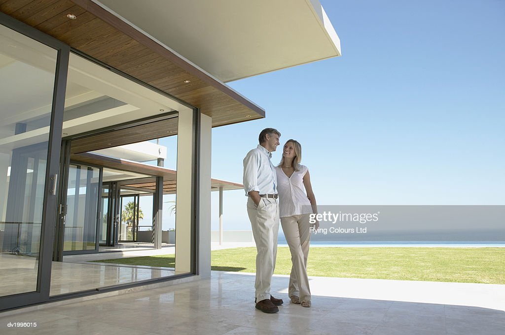 Couple Standing on an Apartment Patio on the Coast : Stock Photo