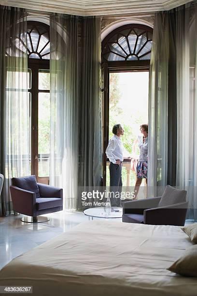 Couple standing on balcony of hotel room