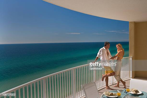 couple standing on balcony overlooking gulf of mexico - a sense of home stock photos and pictures