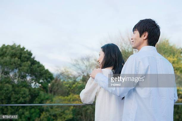 Couple standing on balcony, rear view