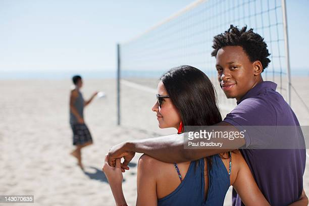 Couple standing on beach volleyball court