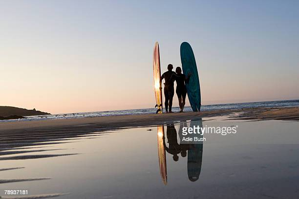 Couple standing on beach with surfboards.