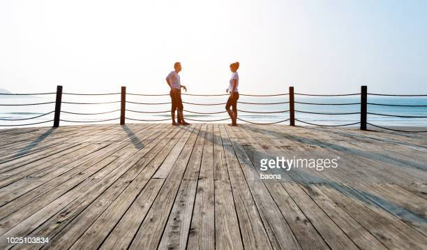 couple standing on boardwalk at the beach - face to face stock pictures, royalty-free photos & images