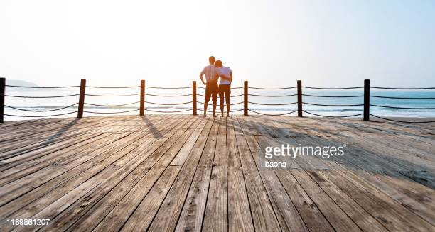 couple standing on boardwalk at the beach - barefoot stock pictures, royalty-free photos & images