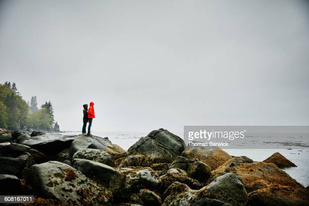 Couple standing on boulders on shoreline of ocean