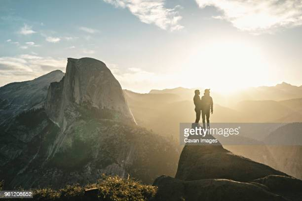 couple standing on cliff against mountains on sunny day - yosemite national park fotografías e imágenes de stock