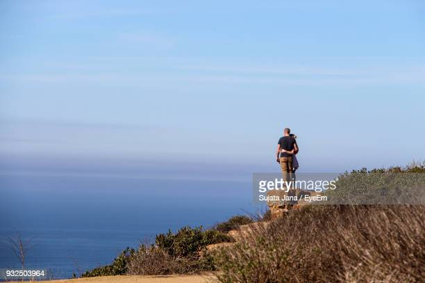 Couple Standing On Cliff Against Sea