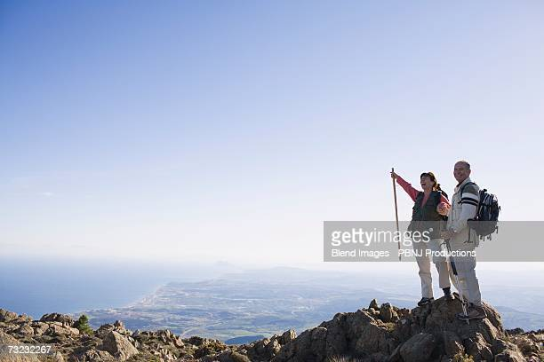 Couple standing on cliff with backpacks