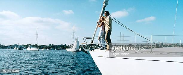 Couple Standing on Deck at the Bow of a Yacht Looking at the View