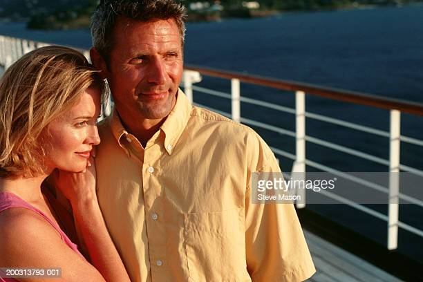 Couple standing on deck of cruise ship at sunset