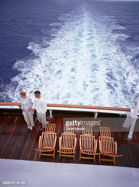 Couple standing on deck of stern of cruise ship, elevated view