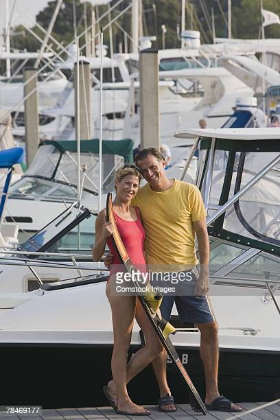Couple standing on dock with water skis