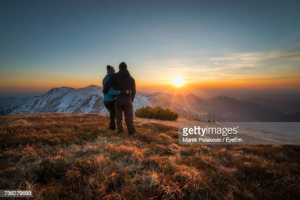 Couple Standing On Field During Sunset