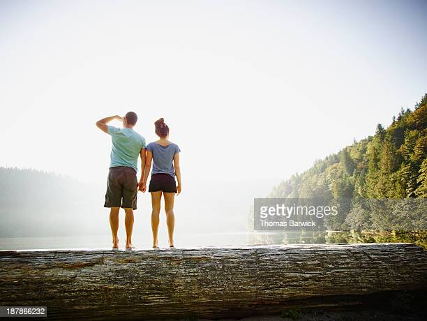 Couple standing on log on lakeshore holding hands