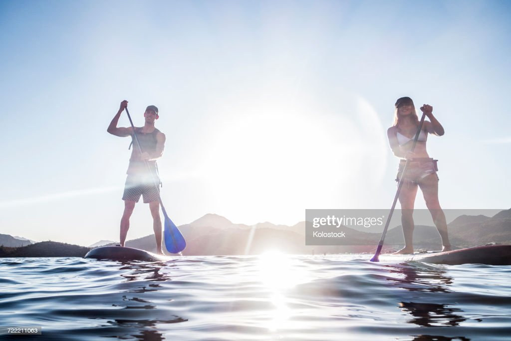 Couple standing on paddleboards in river : Foto de stock