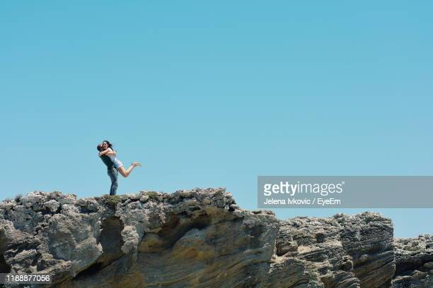couple standing on rock against clear blue sky - jelena ivkovic stock pictures, royalty-free photos & images
