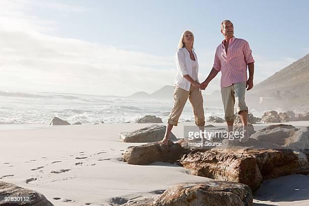 couple debout sur les rochers au bord de la plage - libre de droit photos et images de collection