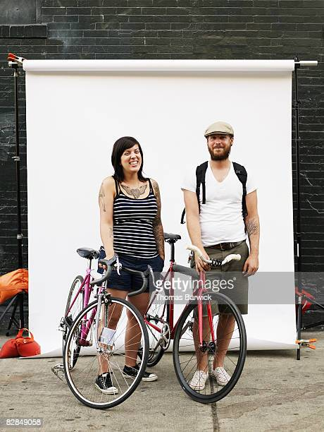 Couple standing on sidewalk holding bikes