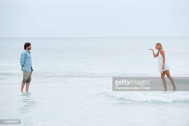 couple standing on surface of water, woman blowing a kiss - middlebare afstand stockfoto's en -beelden
