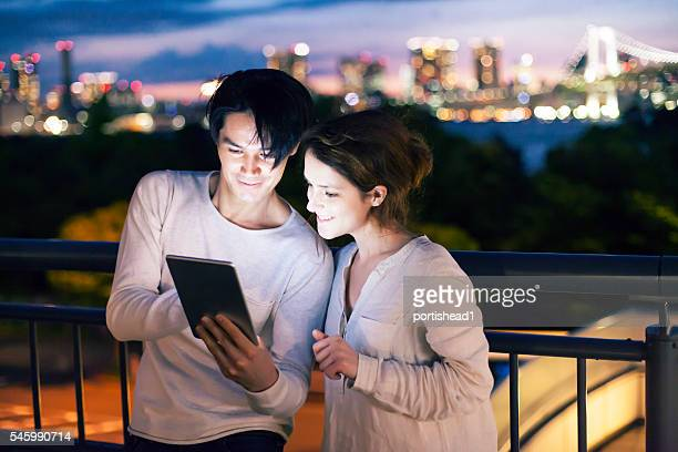 Couple standing on terrace and using digital tablet at night