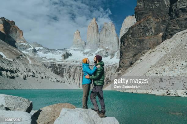 casal em pé ao fundo do parque nacional torres del paine - chile - fotografias e filmes do acervo