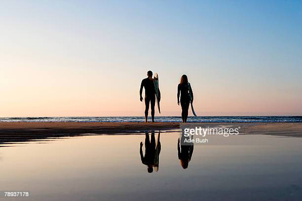 Couple standing on the beach with surfboards.