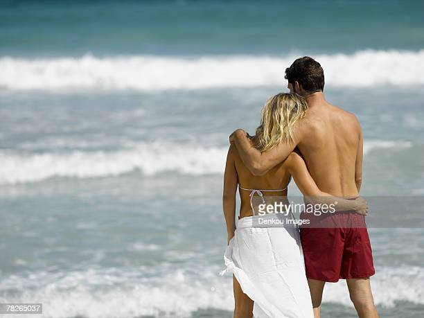 A couple standing on the beach with their arms around each other