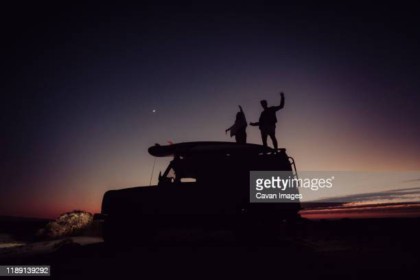 couple standing on top of a 4x4 while camping during the blue hour - blue hour stock-fotos und bilder