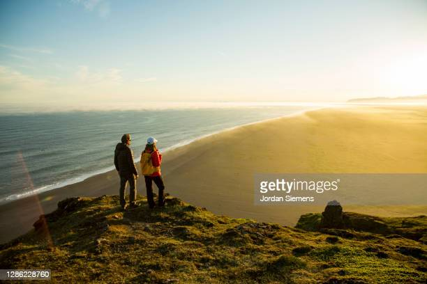a couple standing on top of a cliff overlooking the ocean in iceland. - cliff stock pictures, royalty-free photos & images