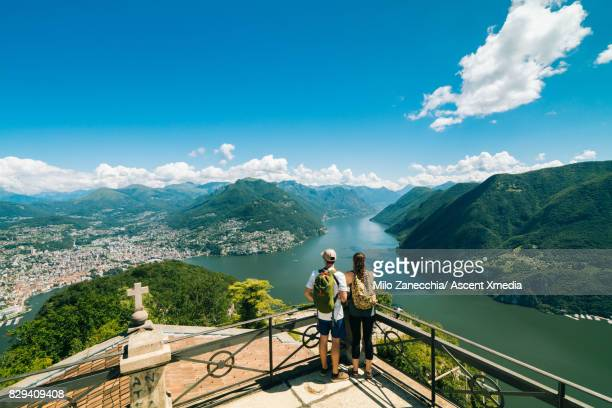 Couple standing on viewpoint overlooking lake and mountains
