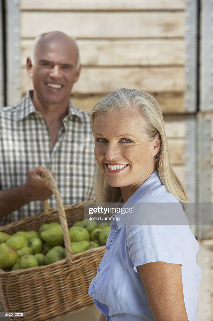 Couple Standing Outdoors, Man Holding a Basket of Pears : Stock Photo