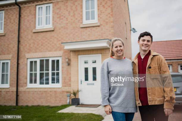 couple standing outside new home - home insurance stock pictures, royalty-free photos & images