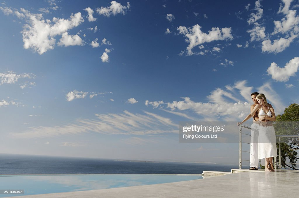 Couple Standing Poolside on a Scenic Coast : Stock Photo