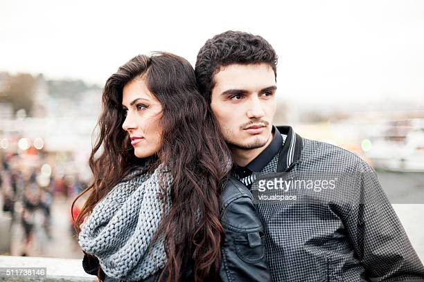 Couple Standing Side by Side on a City Bridge