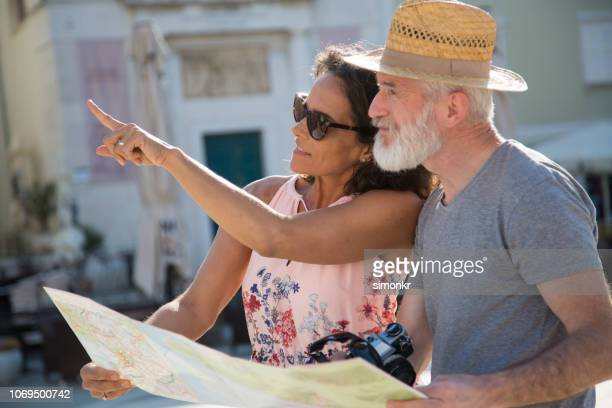 couple standing together and holding map - gray hat stock pictures, royalty-free photos & images