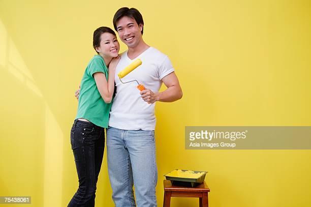 couple standing together, man holding paint roller - côte à côte photos et images de collection