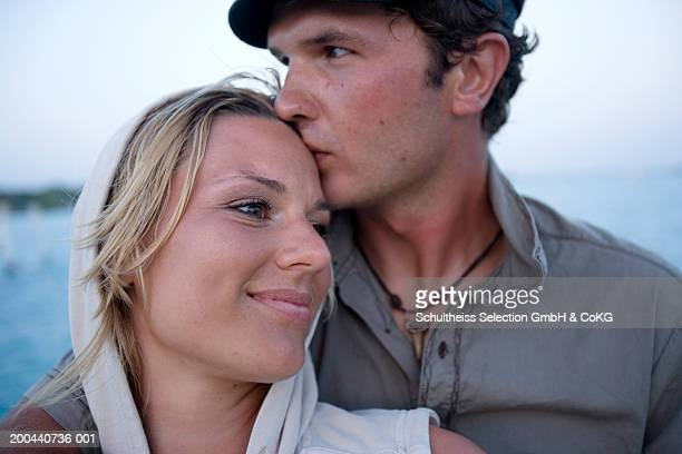 Couple standing together, man kissing woman's close-up