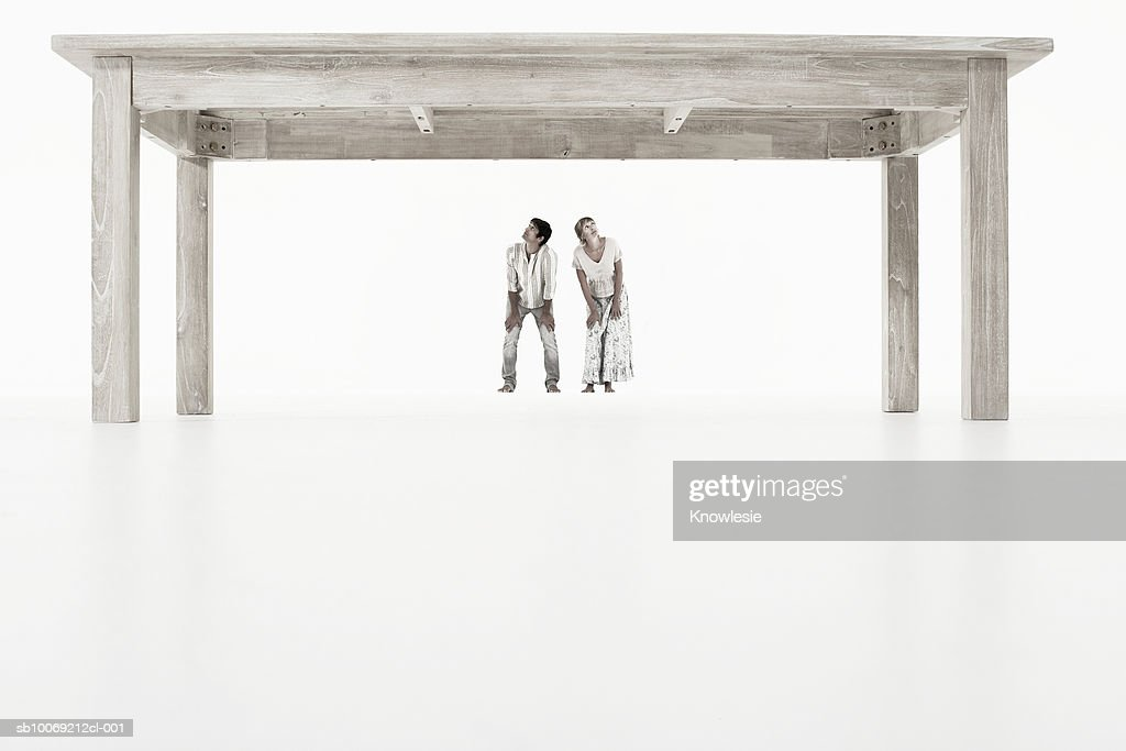 Couple standing under oversized wooden table against white background : Stockfoto