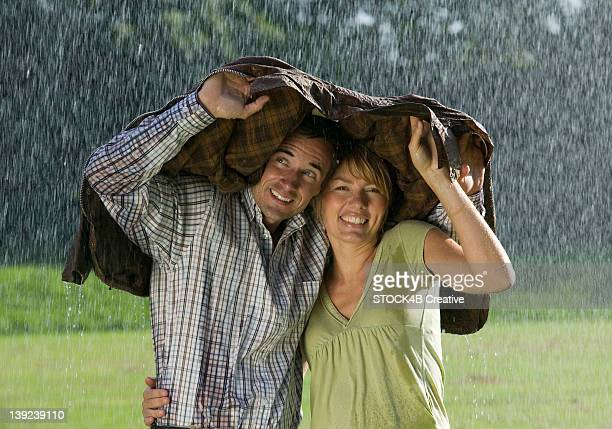 Couple standing underneath a jacket in rain