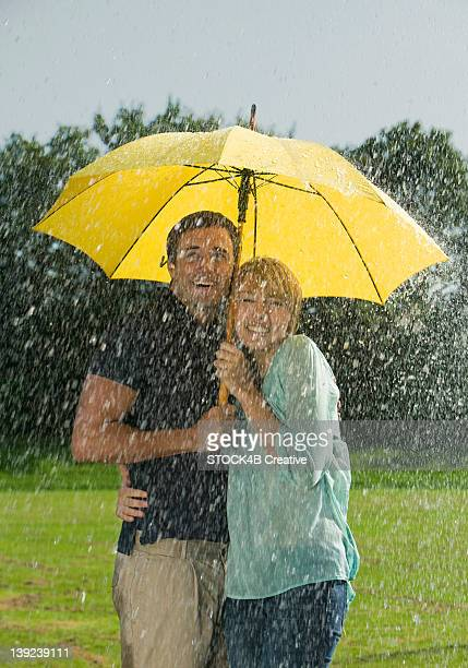 Couple standing underneath umbrella in rain