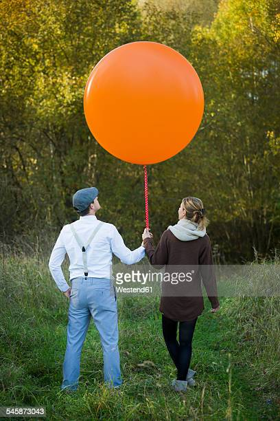 couple standing with balloon on meadow - flat cap stock pictures, royalty-free photos & images