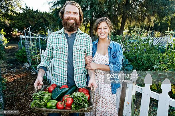 Couple standing with basket of vegetables in garden