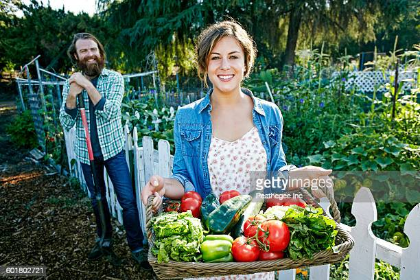 couple standing with basket of vegetables in garden - harvest basket stock pictures, royalty-free photos & images