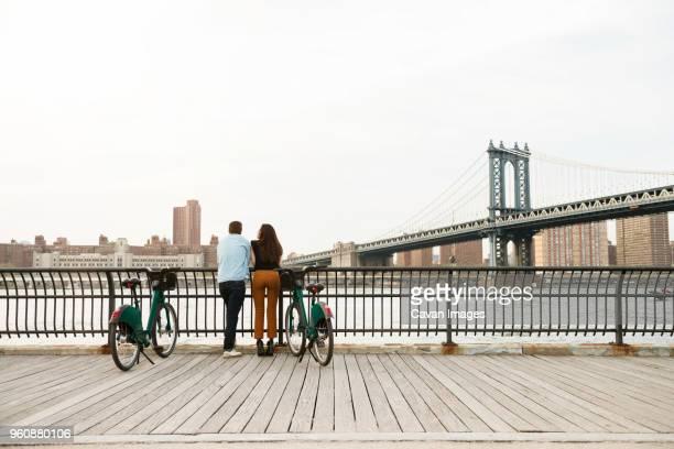 couple standing with bicycles on footpath by manhattan bridge against sky - puente de brooklyn fotografías e imágenes de stock