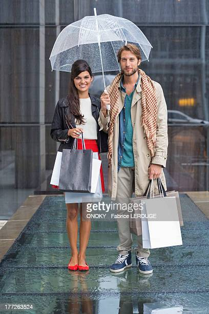Couple standing with shopping bags during rain