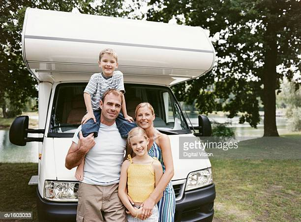 Couple Standing With Their Son and Daughter in Front of Their Mobile Home by a Lake