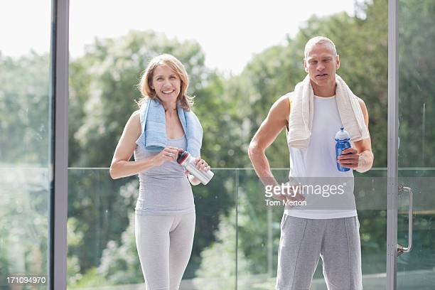 couple standing with towels and water bottles - 40 49 years stock pictures, royalty-free photos & images