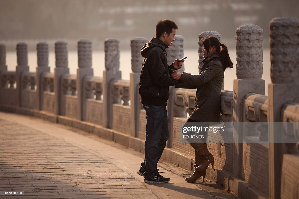 A couple stands beside a lake in Beihai park in Beijing on December 4, 2012. The latest batch of purchasing managers' indexes from HSBC show manufacturing activity in China hit a 13-month high, while India also saw its strongest expansion since June. AFP PHOTO / Ed Jones
